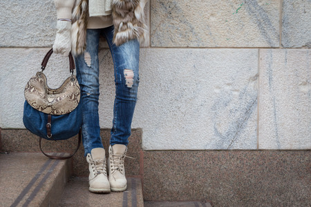 women legs: Detail of a young woman with bag posing in the city streets