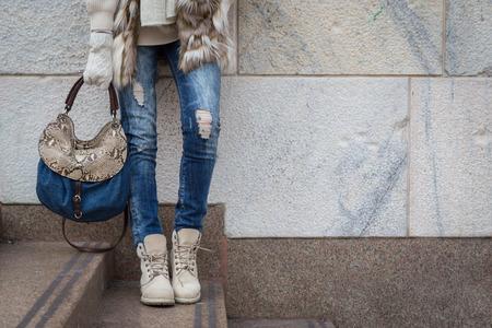 Particolare di una giovane donna con la borsa in posa per le strade della città