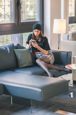 turban: Beautiful young brunette with turban texting on a couch