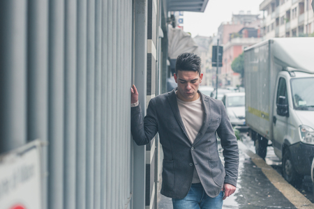 young man short hair: Young handsome man with short hair posing in the city streets Stock Photo