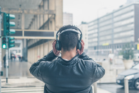 listening back: Back view of a young man with headphones listening to music in the city streets