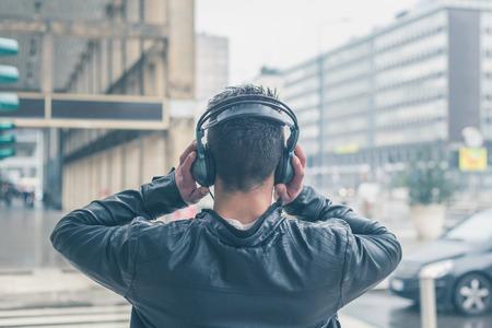 Vista posteriore di un giovane uomo con le cuffie per ascoltare musica per le strade della città