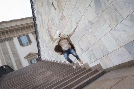 down stairs: Hermosa mujer joven con piel ecológica salta por las escaleras - Concepto de la felicidad, la alegría, la libertad y la diversión Foto de archivo