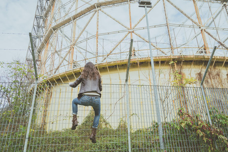 Beautiful young brunette with long hair climbing over a fence Stock Photo
