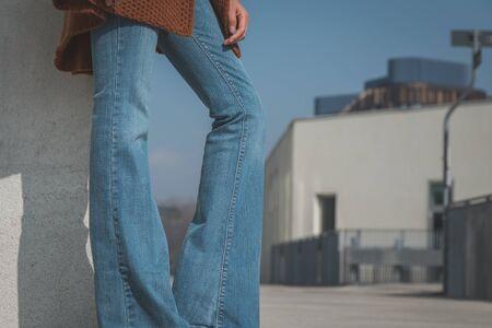 estilo urbano: Detalle de una chica con pantalones vaqueros acampanados y posando en un contexto urbano