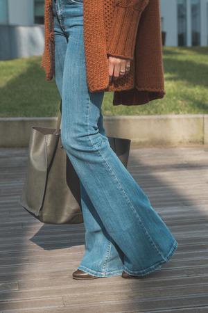 in jeans: Detalle de una chica con pantalones vaqueros acampanados y posando en un contexto urbano
