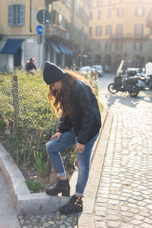 middle eastern: Beautiful Middle Eastern girl with long hair posing in an urban context. Backlight. Stock Photo