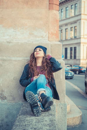 Beautiful Middle Eastern girl with long hair posing in an urban context photo