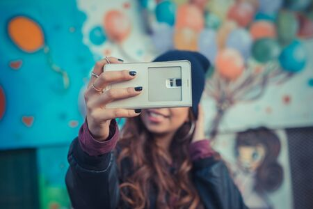 middle eastern: Beautiful Middle Eastern girl with long hair taking a selfie in the city streets