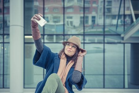 Beautiful young stylish brunette with hat taking a selfie in the city streets photo