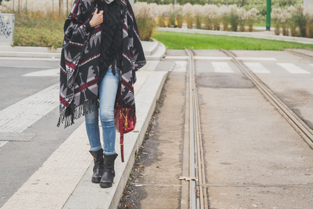 Detail of a young woman with poncho posing in the city streets