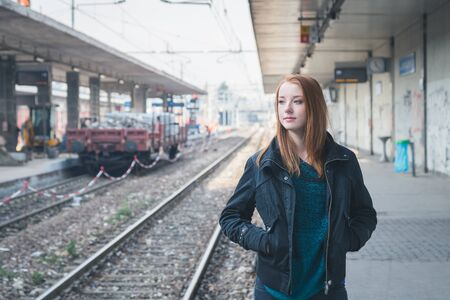 railroad station: Beautiful young redhead girl posing in a railroad station