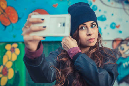 Beautiful Middle Eastern girl with long hair taking a selfie in the city streets photo