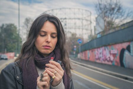 putting lipstick: Beautiful young brunette with long hair putting on lipstick in the city streets Stock Photo