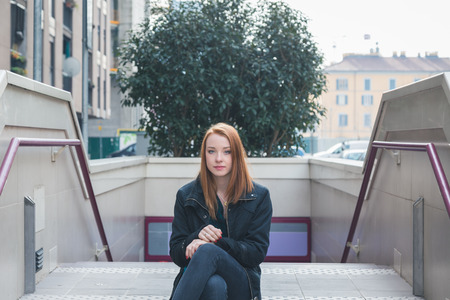 seductive expression: Beautiful young redhead girl posing in the city streets