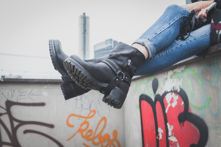 Detail of a young woman wearing black leather biker boots Zdjęcie Seryjne