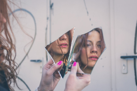 mirror image: Beautiful redhead girl with long hair and blue eyes looking at herself in a broken mirror