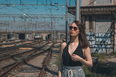 Beautiful young brunette with long hair posing along railroad tracks photo
