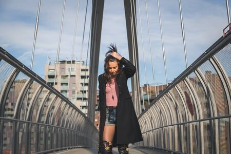 knee boots: Beautiful young brunette with over the knee boots posing on a bridge