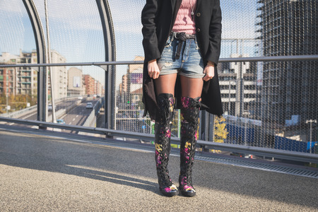 knee boots: Detail of a beautiful young brunette with over the knee boots posing on a bridge Stock Photo