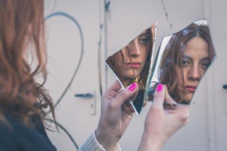 Menina linda ruiva com cabelo comprido e olhos azuis olhando para si mesma no espelho quebrado Imagens