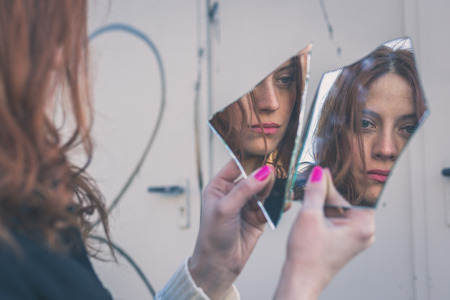 Beautiful redhead girl with long hair and blue eyes looking at herself in a broken mirror