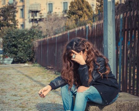middle eastern: Sad Middle Eastern girl with long hair posing in an urban context
