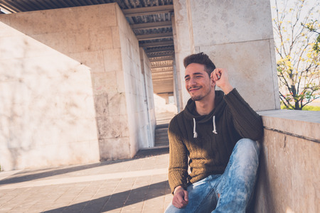 young man short hair: Young handsome man with short hair posing in an urban context Stock Photo