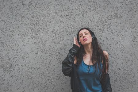 moda mujer: La muchacha hermosa con los auriculares escuchando m�sica en las calles de la ciudad