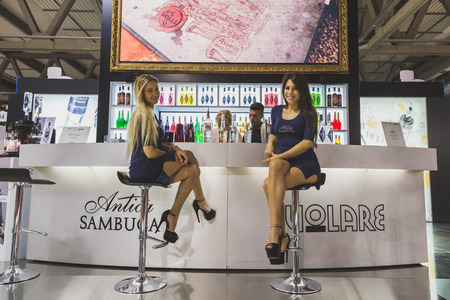 culinary tourism: MILAN, ITALY - MAY 4: Two pretty girls working at Tuttofood, world food exhibition on MAY 4, 2015 in Milan.