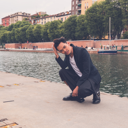 philippine adult: Young handsome Asian model dressed in black posing by an urban artificial basin