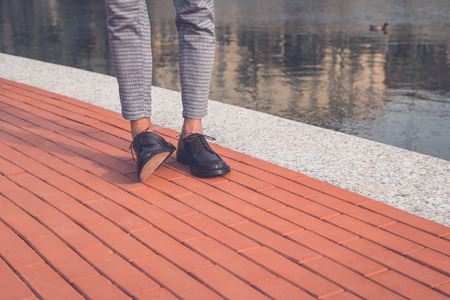 artificial model: Detail of the shoes of a young handsome Asian model posing by an urban artificial basin