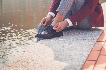philippine adult: Detail of the shoes of a young handsome Asian model posing by an urban artificial basin