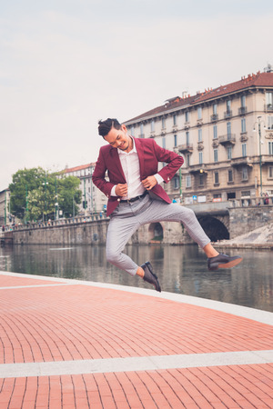 philippine adult: Young handsome Asian model dressed in red blazer jumping by an artificial basin