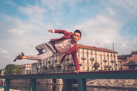 modelos posando: Modelo asiático hermoso joven vestido con chaqueta roja saltando una balaustrada Foto de archivo