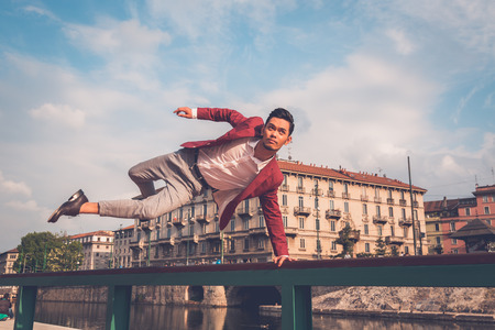 filipino people: Young handsome Asian model dressed in red blazer jumping a balustrade