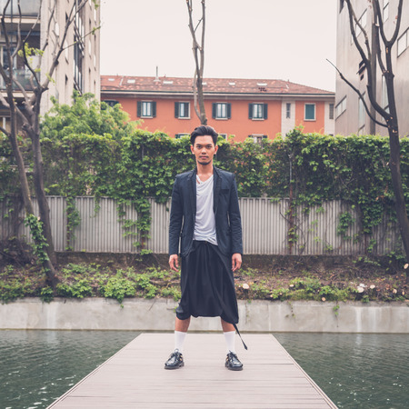 artificial model: Young handsome Asian model dressed in black posing by an urban artificial basin
