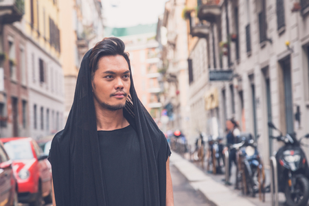 tunic: Young handsome Asian model dressed in black tunic posing in the city streets Stock Photo