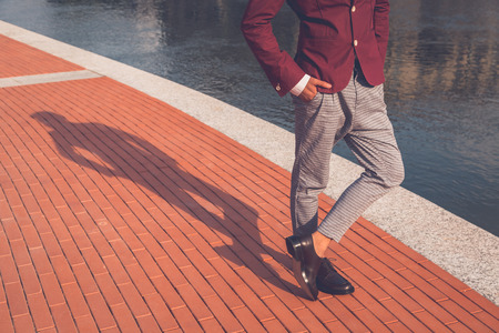 Shadow of an Asian model dressed in red blazer posing by an artificial basin
