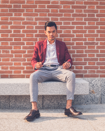 philippine adult: Young handsome Asian model dressed in red blazer sitting on a marble bench in the city streets Stock Photo
