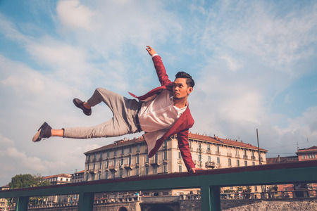Young handsome Asian model dressed in red blazer jumping a balustrade