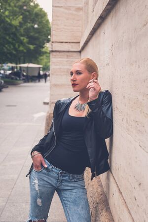 ripped jeans: Beautiful blonde girl wearing ripped jeans and leather jacket smoking a cigarette in the city streets Stock Photo