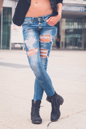 girls in jeans: Detail of a young woman in ripped jeans posing