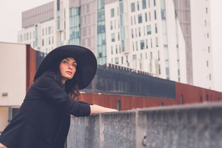 context: Gorgeous young brunette with hat posing in an urban context Stock Photo