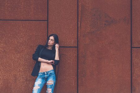 rusty background: Gorgeous young brunette in jeans posing on a rusty background