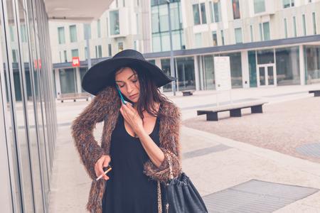 Gorgeous young brunette in black dress talking on phone in an urban context photo