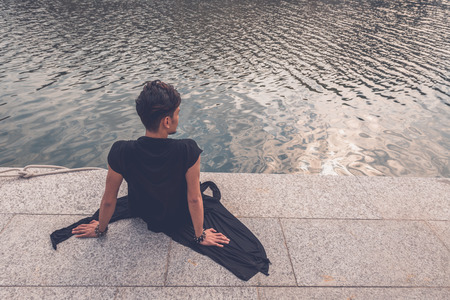 philippine adult: Young handsome Asian model dressed in black tunic sitting by an artificial basin Stock Photo