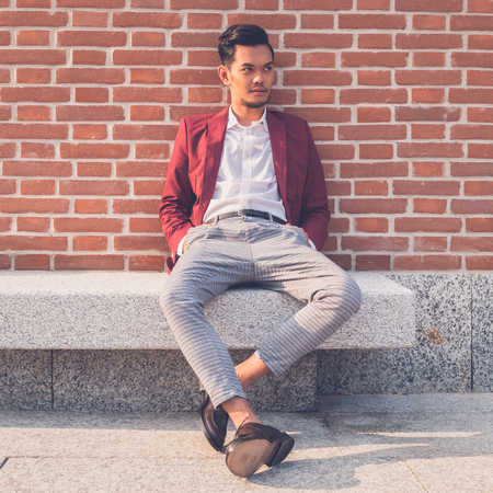 Young handsome Asian model dressed in red blazer sitting on a marble bench in the city streets Zdjęcie Seryjne