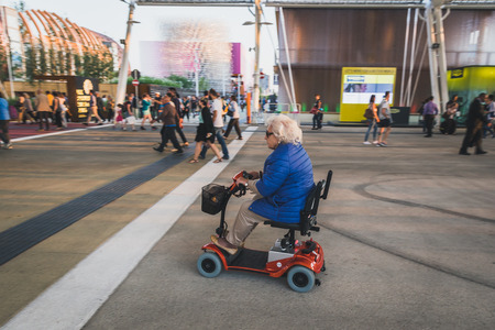 MILAN, ITALY - MAY 27: Elderly woman on electric mobility scooter at  Expo, universal exposition on the theme of food on MAY 27, 2015 in Milan.