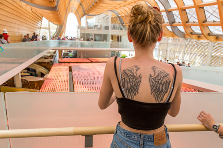 showcase interiors: MILAN, ITALY - JUNE 5: Girl with tattoo visits China pavilion at Expo, universal exposition on the theme of food on JUNE 5, 2015 in Milan.